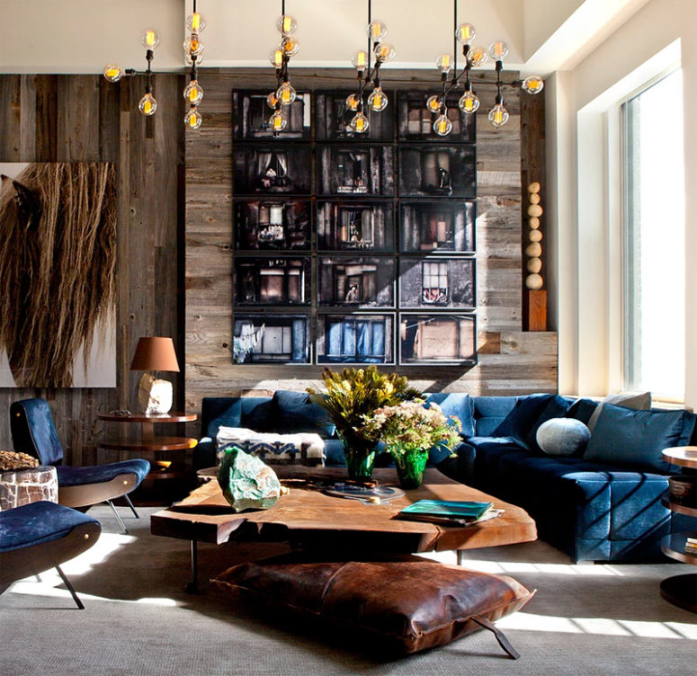 The living room features navy velvet furniture, a raw edge coffee table and a laether pillow, a weathered wood wall is a great solution