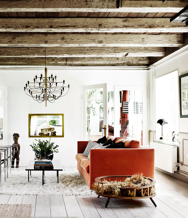 The living room features wooden beams and a bold orange sofa, fur pieces add coziness and texture