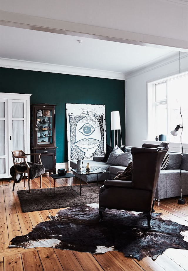 The living room is done in white and teal, with light-colored wooden floors, brown and grey furniture, with a statement wall art piece in black and white