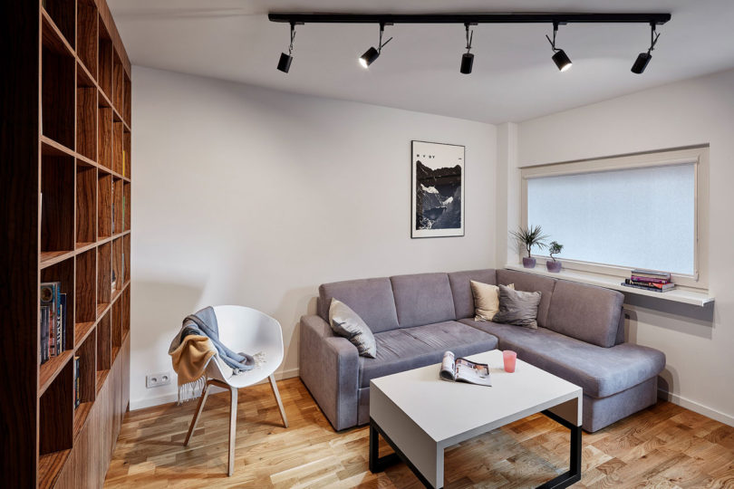 There's a grey corner sofa, a white coffee table and a large wooden bookcase, and though the window is small, white walls make the space light