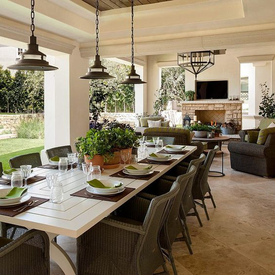 a beautiful outdoor covered porch with a large table for entertaining and a separate living area with fireplace - feels like an indoor extension