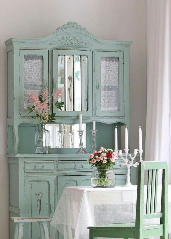 a mint vintage cupboard with mirror parts and tulle curtains inside the compartments