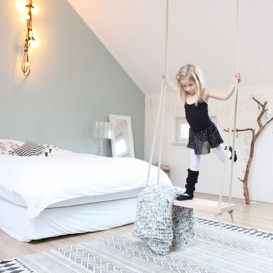 a swing in a serene and light-colored girl's room is a storage piece and a play piece in one