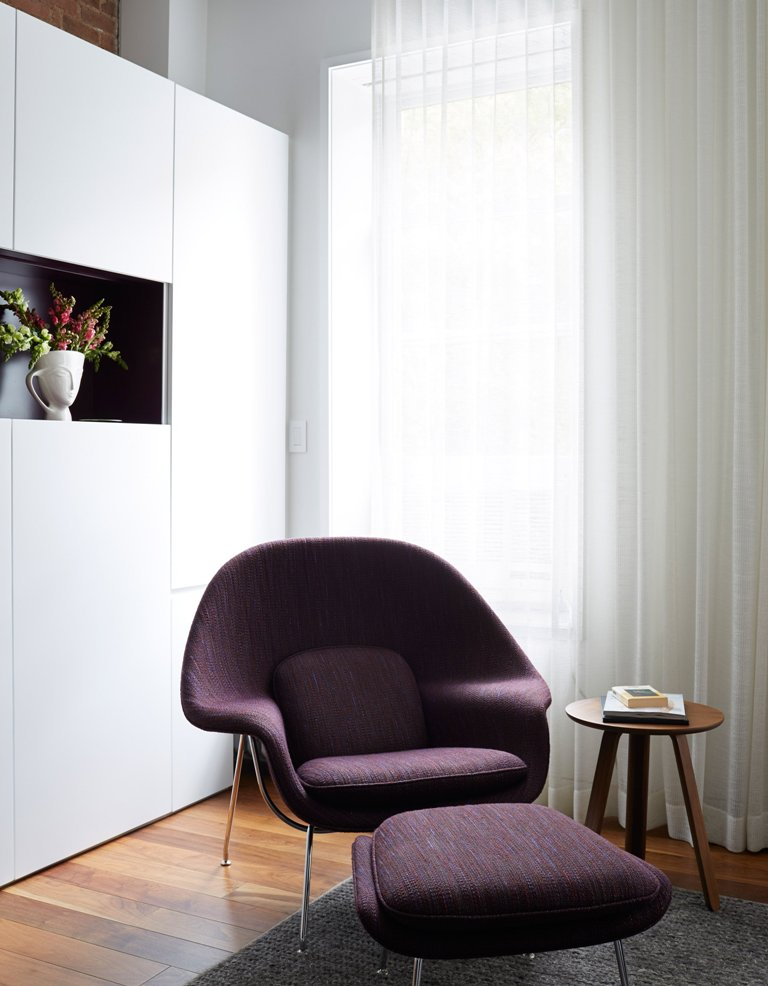 A long range of white cabinets along one wall gives much storage space and there's an open purple niche