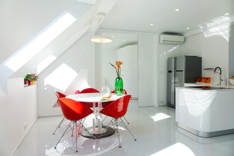 The attic kitchen is all-white, with a corner cooking space and a small dining area by the window