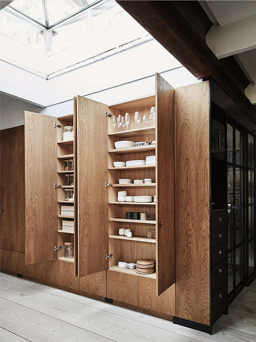 The built-in tall wooden cabinets are a comfy solution to accomodate a lot of things