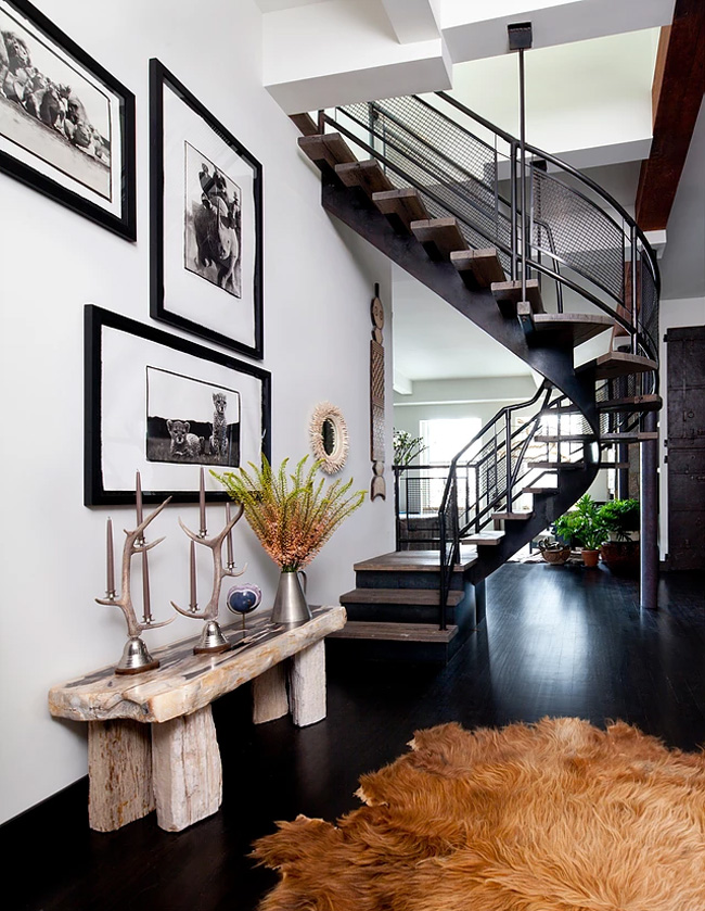 The entryway has a cool staircase, a faux fur rug and a rough wood bench