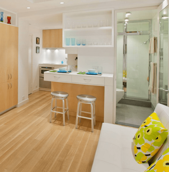 The small kitchen features white countertops and lots of drawers for storage, they hide the bathroom partly