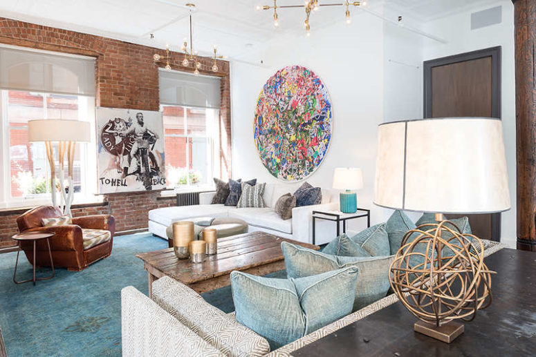 A bold abstract wall art adds eye-catchiness to the space, and a leather chair and a shabby coffee table add texture