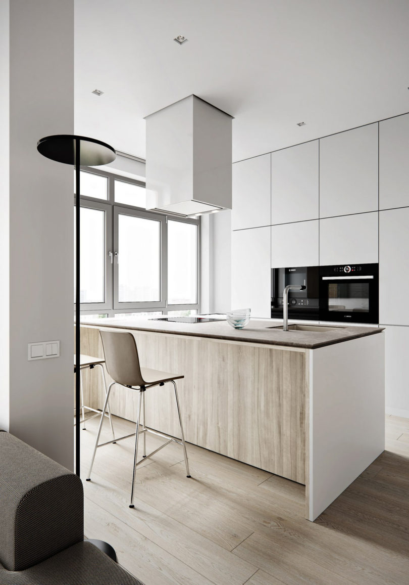 The kitchen features light colored cabinets with no handles, a large kitchen island that doubles as a dining table