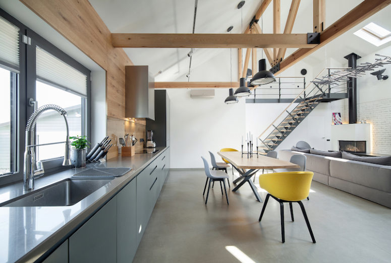 The kitchen has large windows and a grey color palette, while the dining space is accentuated with bold yellow chairs
