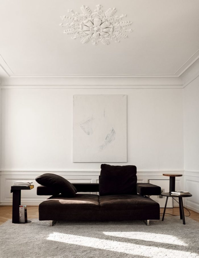 The living room features a gorgeous stucco ceiling, and a black sofa and a fluffy rug give texture and make it more inviting