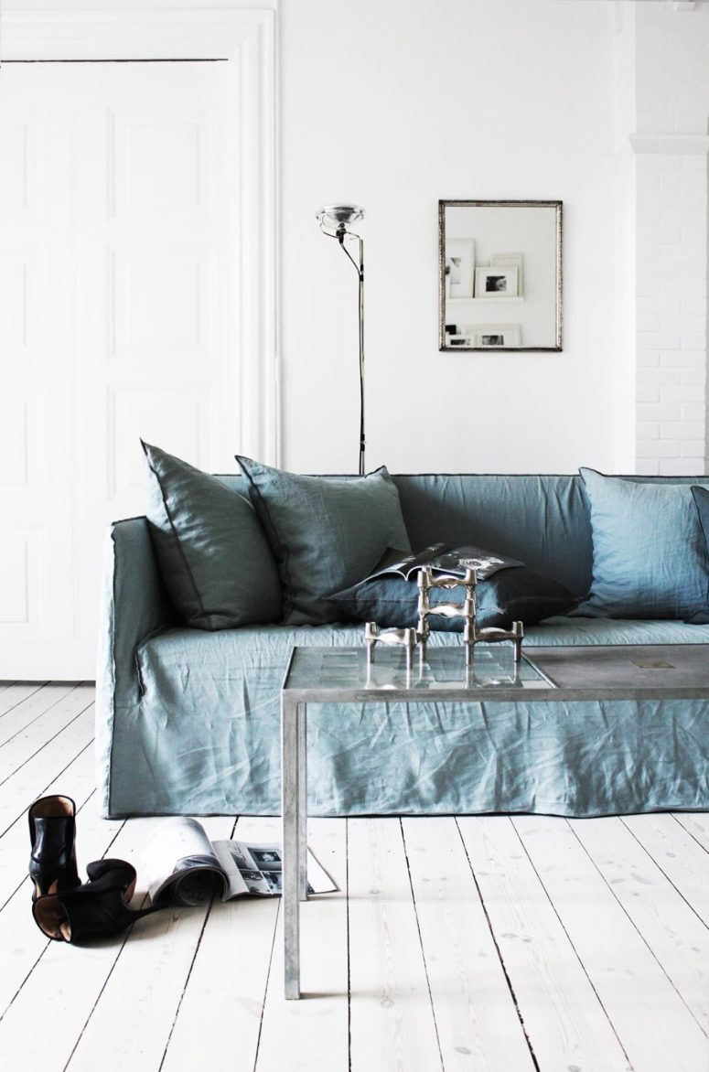 There are some colorful touches done with furniture, for example, this dusty blue sofa with pillows, which perfectly accentuates the space