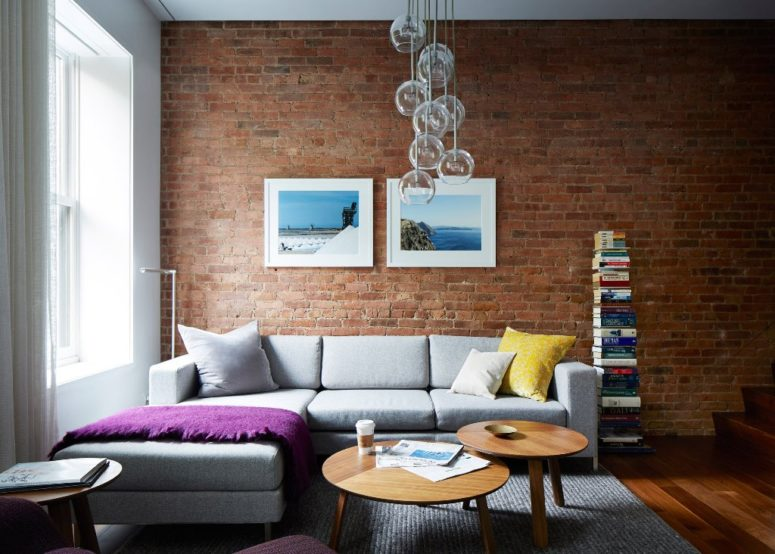 A grey sofa contrasts an exposed brick wall, there's a bubble pendant lamp and an open bookshelf