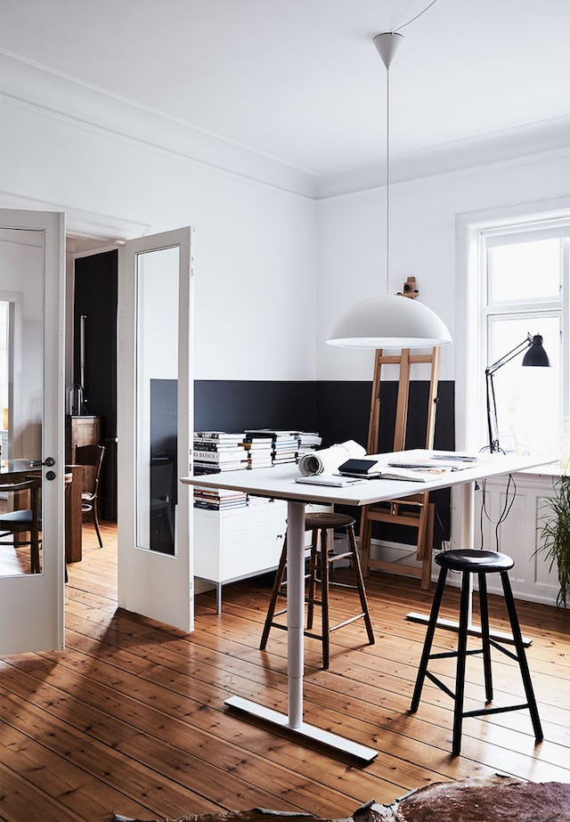 The home office is small, it's designed in black and white, with a large desk and stools, a credenza is also with a stack of books