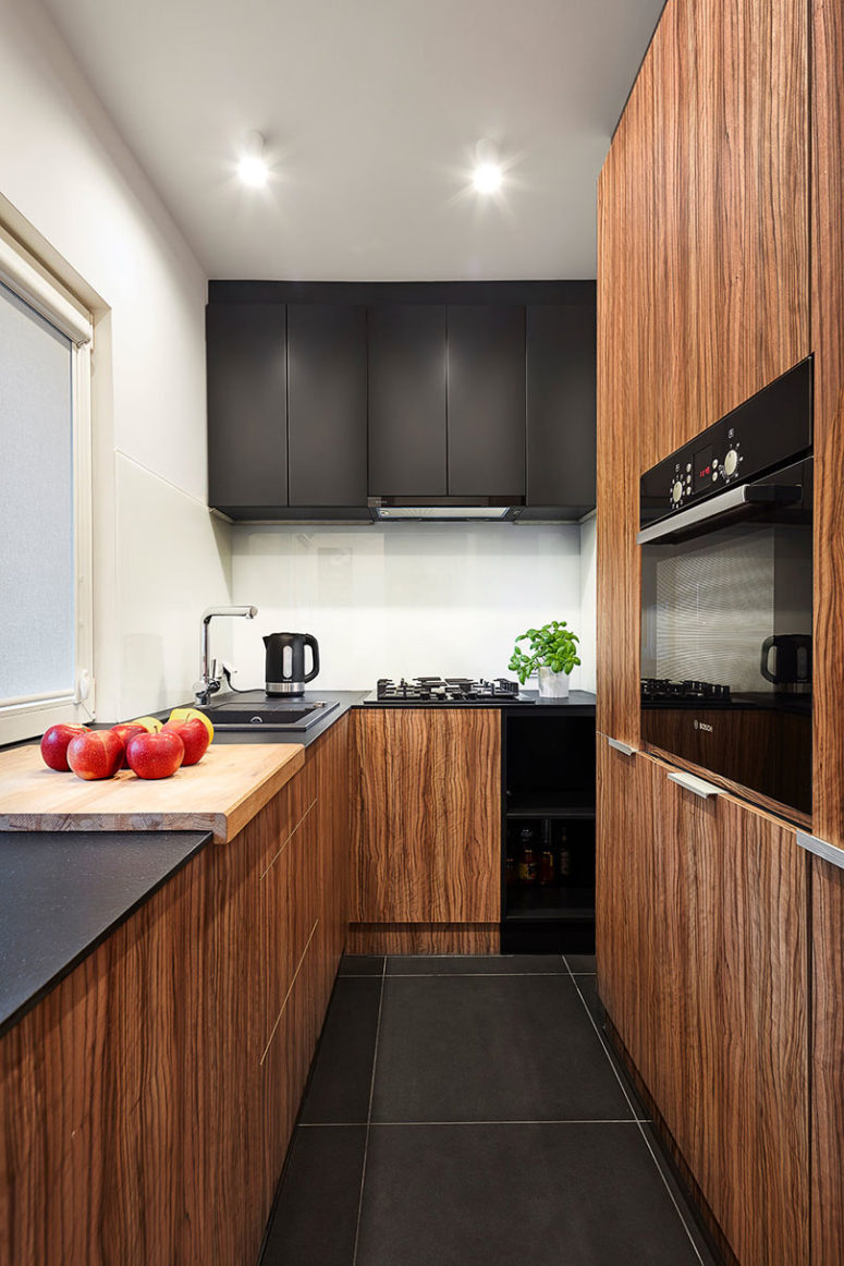 The kitchen is also small, it features white walls and a backsplash and black and warm wood cabinets for a contrasting look