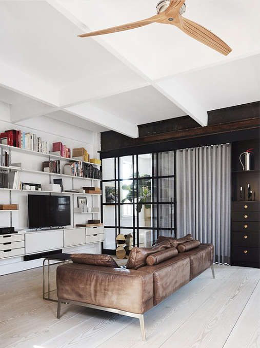 The living room is separated from the open layout with a black framed metal and glass door, it's done in black and white and there's a leather sofa