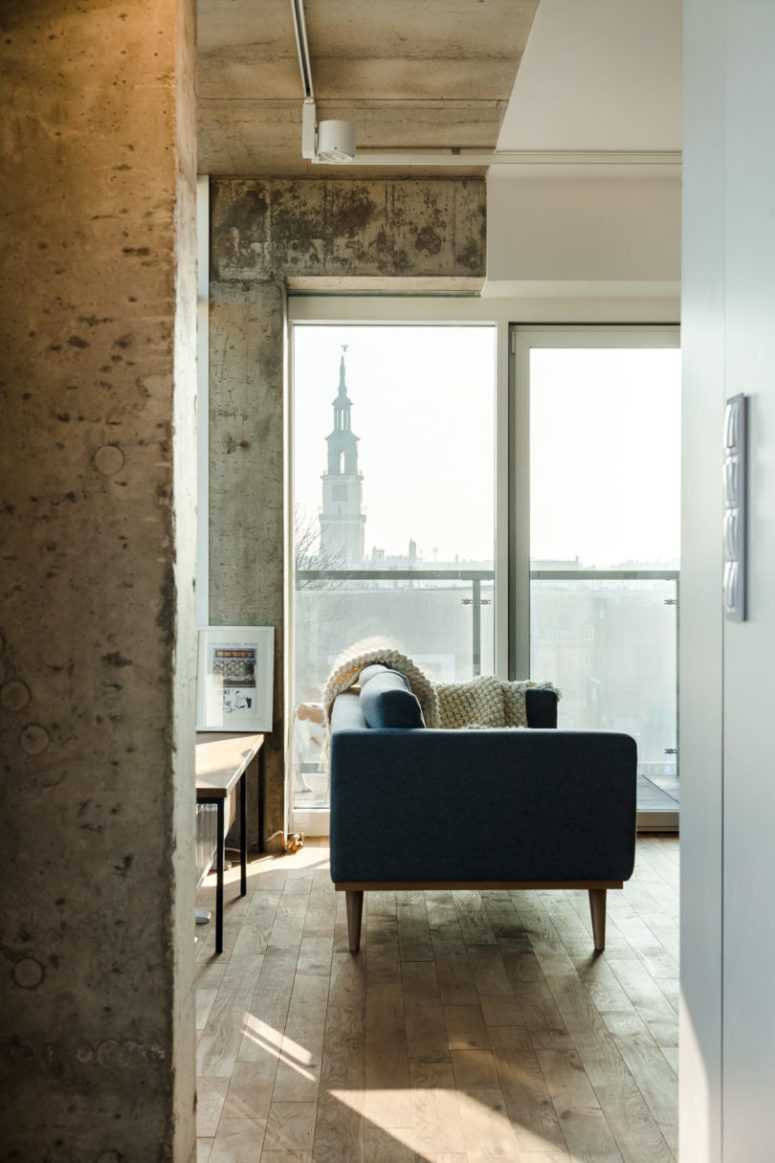 The walls are rough concrete for an industrial feel, and the floors are clad with wood for a warm touch