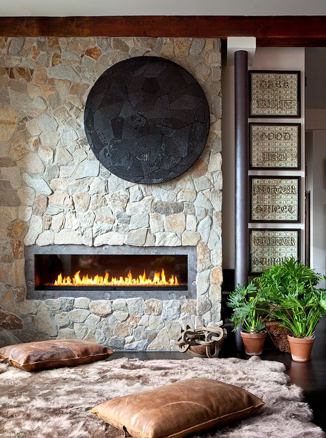 There's a fireplace built-in a wall covered with real stone, here there's a fluffy rug and pilloows to enjoy it