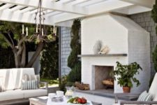 05 a coastal-inspired outdoor living room with a chandelier and a fireplace and neutral upholstery