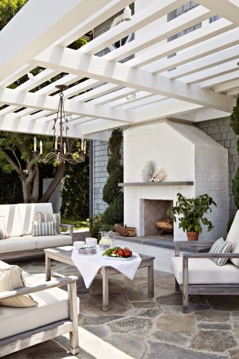 a coastal-inspired outdoor living room with a chandelier and a fireplace and neutral upholstery