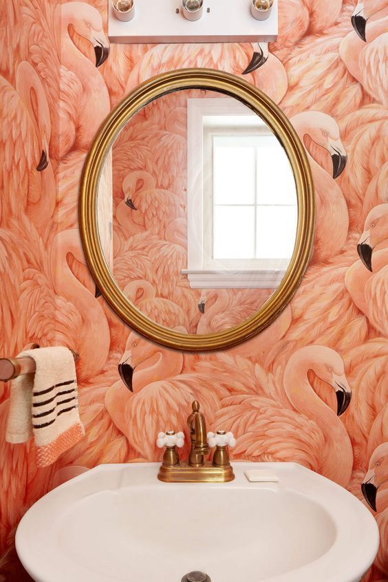 coral flamingo wallpaper in a powder room looks interesting with gold fixtures