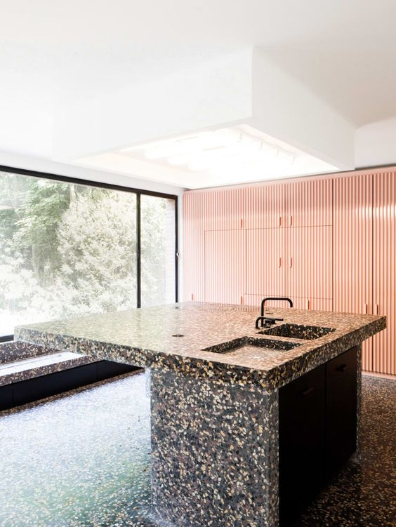 dark terrazzo kitchen island and floor look like a monolith