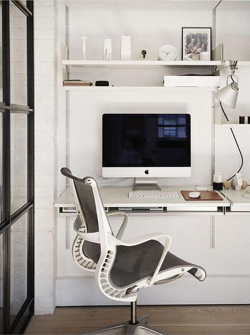 A small home office nook is done in pure white, with a chic modern chair and some shelves