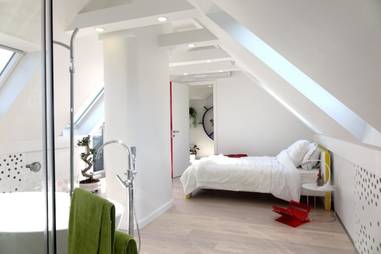 One of the attic bedrooms features an open bathroom with a bathtub, a shower and a sink with a stand