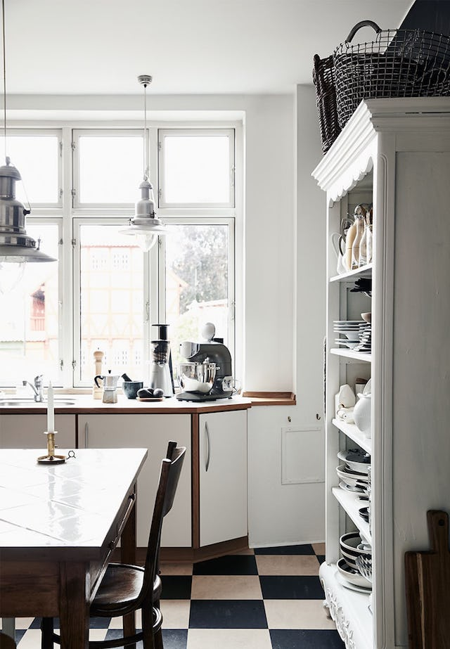The kitchen is mostly white and only the floors are contrasting in black and white, there are natural wood touches to soften the space