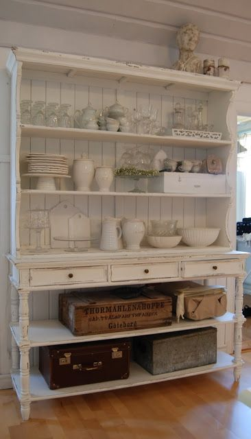a white shabby chic cupboard without glass parts accomodates a lot of things