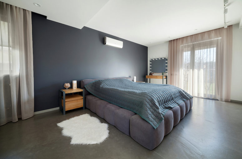the master bedroom is spacious and has a unique upholstered bed and again a grey color palette