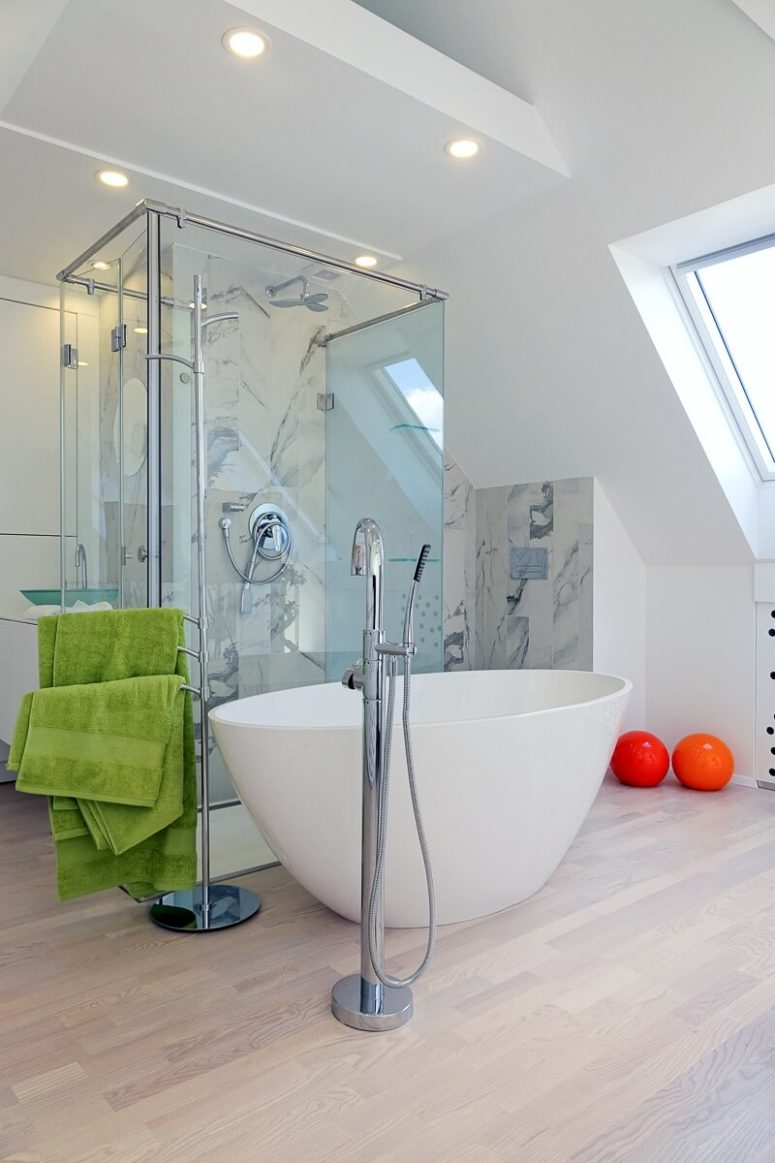 A bathtub in a bedroom is a hot decor trend, this area is clad with marble-inspired tiles