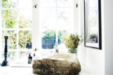The bathroom has framed windows and a stunning rough wood sink contrasting with modern surroundings