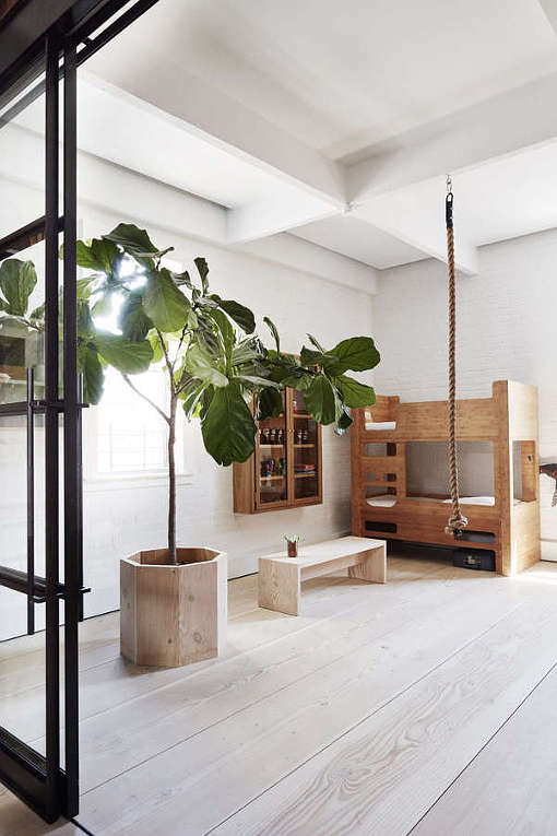 The kid's space continues the loft decor style with white brick walls, simple wooden furniture and a framed glass door
