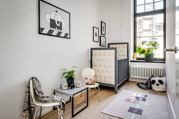 The nursery is creamy and grey, with an upholstered kids bed, a cozy rug and some artworks