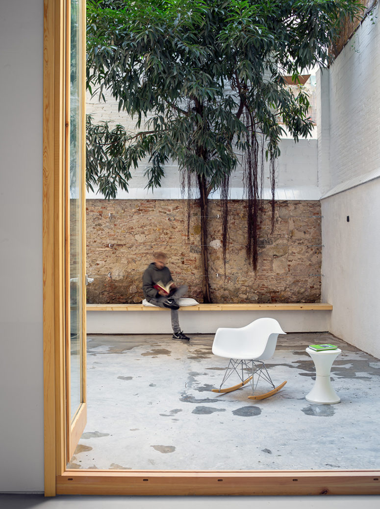 The patio is decorated in a minimalist way, with a long wooden bench and some modern furniture