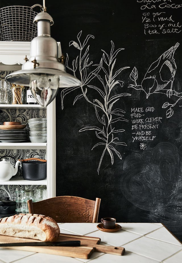 The sideboard features black and white wallpaper and there's a chalkboard wall for leaving messages