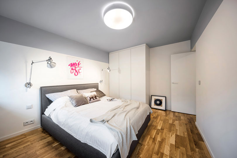 There's an upholstered grey bed and a white storage unit in the corner, the decor is practical and aimed at relaxing