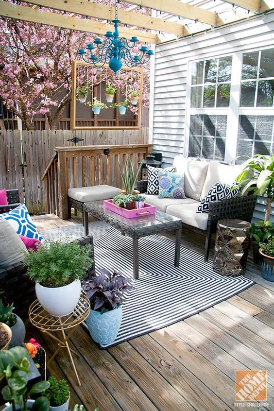 colorful outdoor living room on the porch with patterns, prints and potted greenery