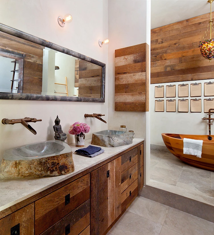 The bathroom features much weathered wood, a wodoen bathtub and stone sinks that catch an eye