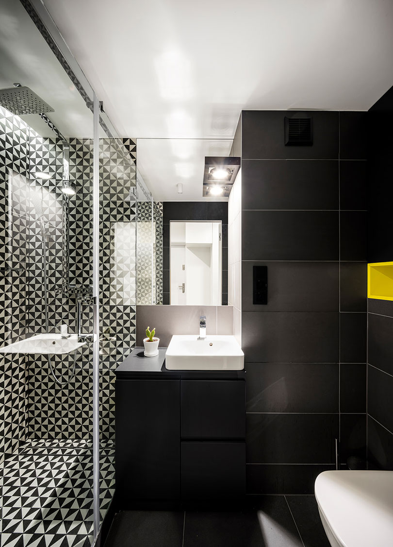 The bathroom is done in matte black and with graphic geo print tiles in the shower, it looks modern and very chic