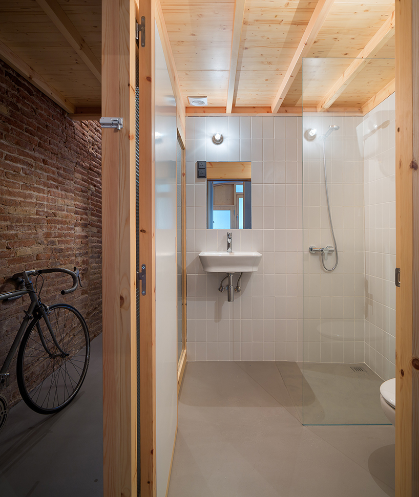 The bathroom is neutral, with white tiles and a concrete floor, wood makes it cozier