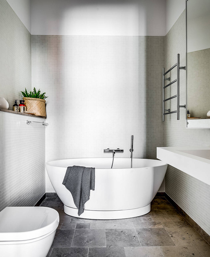 The bathroom is small yet very relaxing, with an oval-shaped bathtub and dove grey tiles