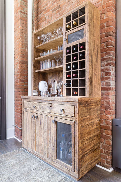 The home bar is made of reclaimed wood, there are open shelves and drawers
