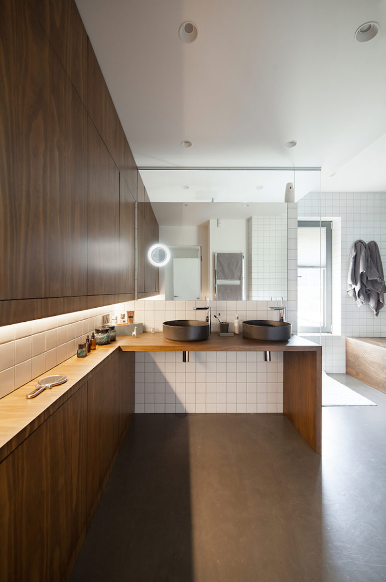 The master bathroom is big and very open, there's a cool wooden countertop with sinks and storage