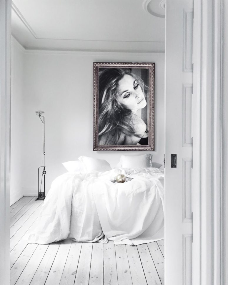 The master bedroom features a large comfy bed and an oversized framed portrait of the owner, which makes the space gorgeous and refined