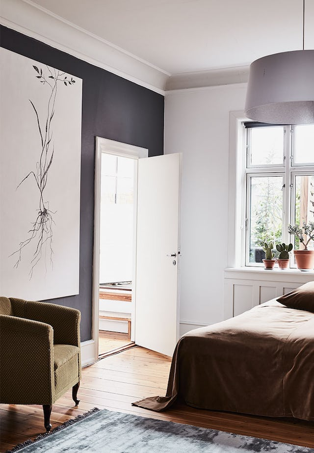 The master bedroom is rather simple and soft, charcoal grey and white, with wooden floors and a cozy mustard-colored chair