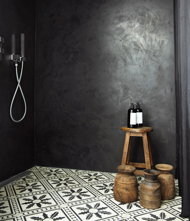 The shower is done in black and graphic floor tiles, wooden accessories add warmth