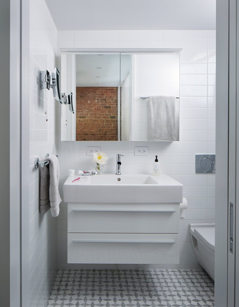 The bathroom is clad with white tiles, and the floor is done in grey graphic tiles, everything here is functional